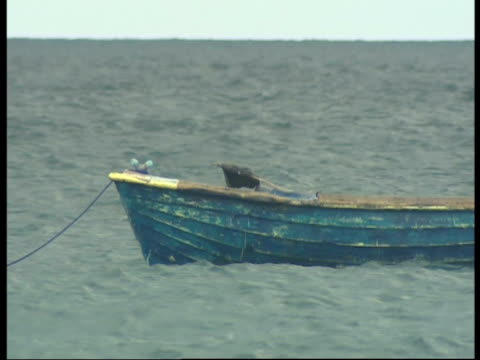 vídeos de stock, filmes e b-roll de an empty boat rocks in the ocean off the coast of sri lanka - ancorado