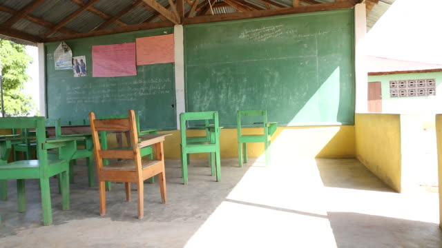 of an empty classroom in a school in ouanaminthe, haiti. multiple chairs and desks can be seen in front of a chalkboard. - chair stock videos & royalty-free footage