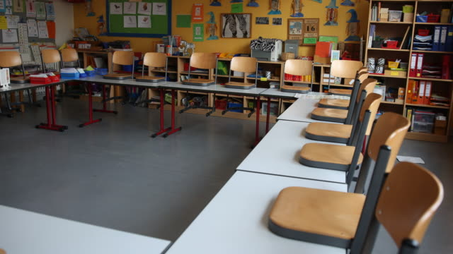 vídeos y material grabado en eventos de stock de an empty classroom in berlin, with the chairs placed on the tables following a city ordinance temporarily closing all non-essential shops and... - entrenar