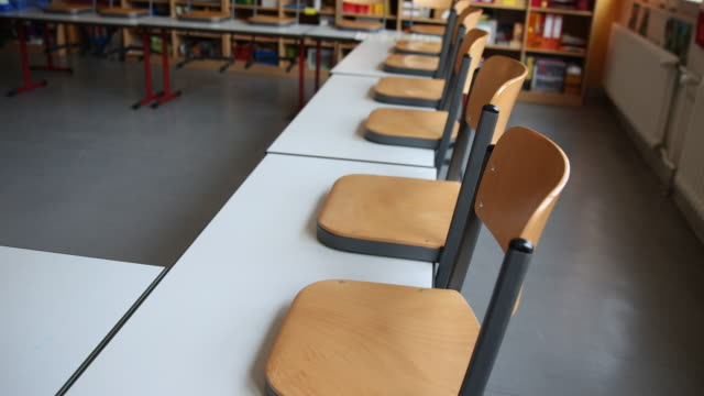 an empty classroom in berlin, with the chairs placed on the tables following a city ordinance temporarily closing all non-essential shops and... - non urban scene stock-videos und b-roll-filmmaterial