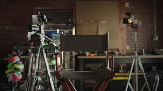 stockvideo's en b-roll-footage met slo mo. an empty director's chair sits between a camera tripod and a light stand on an independent film set. - decor