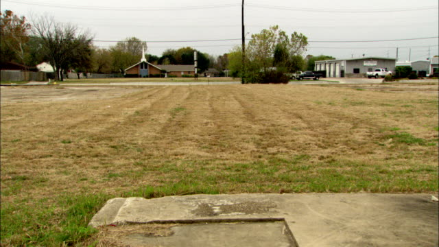 An empty, grassy lot borders a neighborhood.