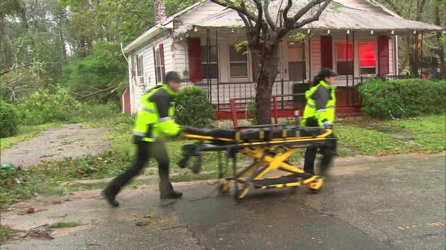 an empty gurney is wheeled to a house by medical personnel in the aftermath of hurricane florence on september 14, 2018 in wilmington, north carolina. - wilmington north carolina stock videos & royalty-free footage