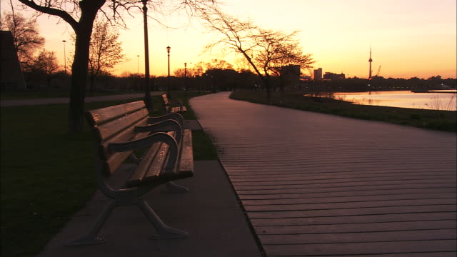 an empty park benches face a wide footpath on a waterfront. - bench stock videos & royalty-free footage