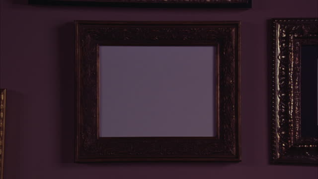 vídeos de stock e filmes b-roll de an empty picture frame hangs next to photographs of martin luther king, jr. and others on a plum-colored wall. - imagem