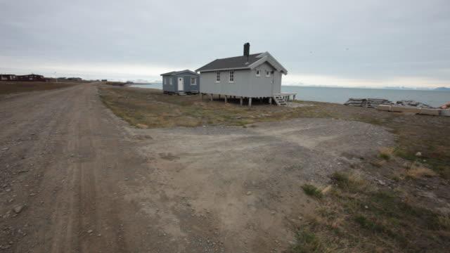 An empty road and a few houses at Adventfjorden near Longyearbyen airport, Svalbard archipelago