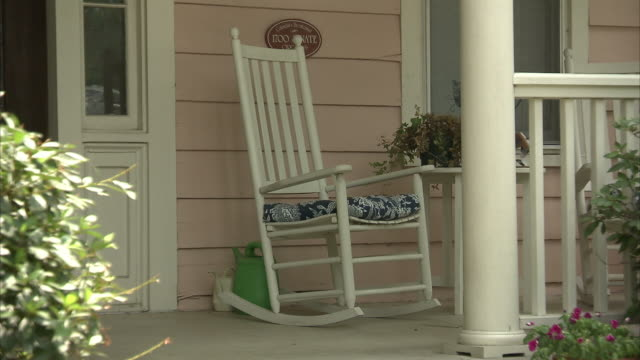 an empty rocking chair sits on the front porch of a home. - chair stock videos & royalty-free footage