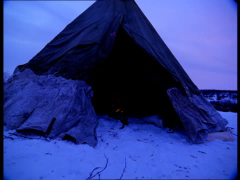 An empty tee-pee, with a fire inside, stands on a snowy plain in Norway.