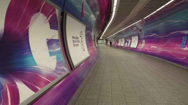 an empty walkway at king cross underground station with 11g advertising during the coronavirus covid-19 pandemic. the prime minister announced the... - advertisement stock videos & royalty-free footage