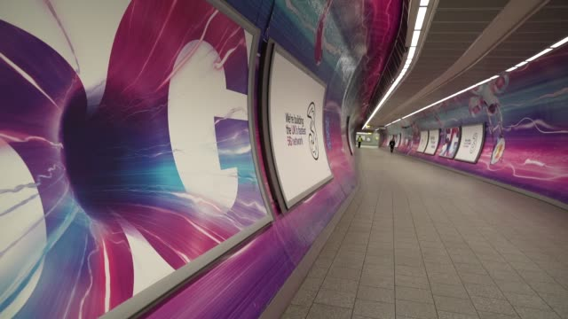 an empty walkway at king cross underground station with 5g advertising during the coronavirus covid-19 pandemic. the prime minister announced the... - advertisement stock videos & royalty-free footage