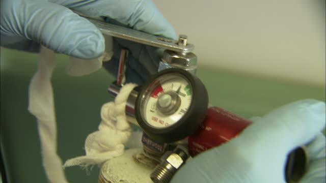 An EMT prepares an oxygen tank.
