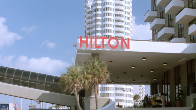 an enclosed walkway joins a portico at the entrance to a hilton hotel. - 1990 stock videos & royalty-free footage