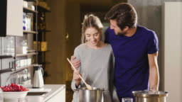An engaged couple cook together and have fun while tasting the sauce they have prepared. The married couple embraces to show their love.