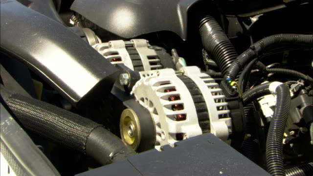 an engine starts up and a belt spins an alternator. - belt stock videos & royalty-free footage
