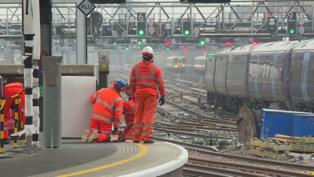 an engineer looks on as a train moves away from a platform at london bridge station during engineering works. - engineering stock videos & royalty-free footage