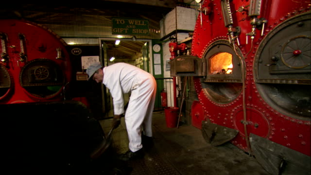 an engineer shovels coal into a furnace at the crofton pumping station in marlborough united kingdom. available in hd. - digging stock videos & royalty-free footage