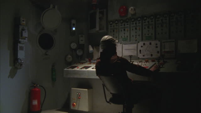 vidéos et rushes de an engineer sits in the control room of a ship. - hublot