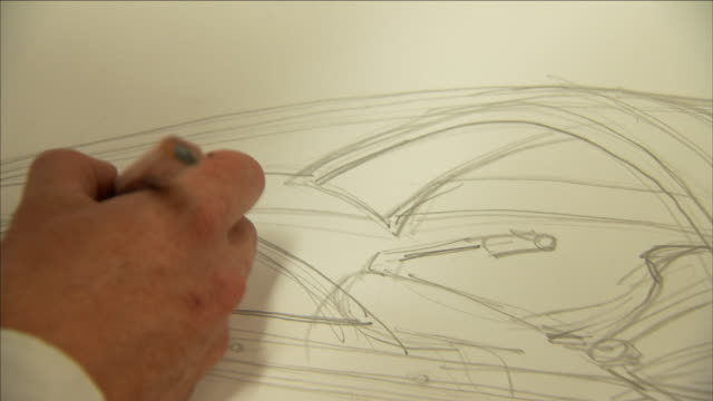vídeos de stock e filmes b-roll de an engineer sketches on the design of the seabreacher. - conceito