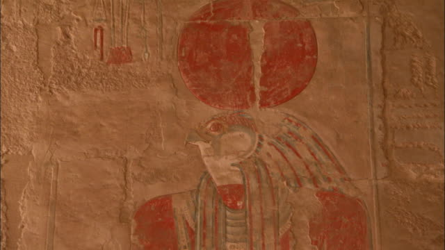 an engraving depicts an egyptian woman standing near the god horus on a temple wall at deir el-bahari in egypt. available in hd. - tempio di hatshepsut video stock e b–roll