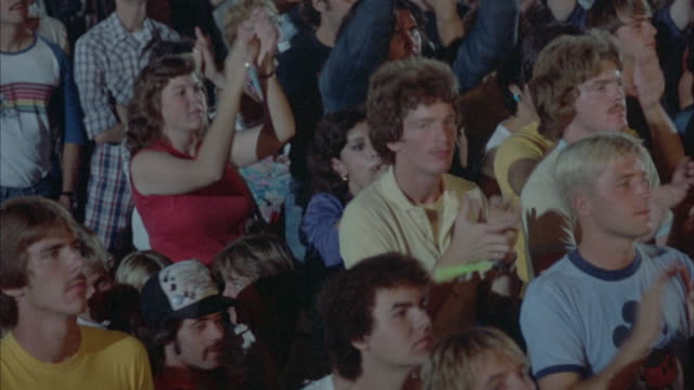 an enthusiastic audience raising arms and clapping at a concert. - rock stock-videos und b-roll-filmmaterial