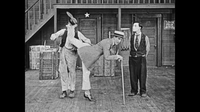 1919 an enthusiastic vaudeville dancer (jack coogan sr.) accidentally kicks man (al st john) to the ground and knocks the hat off of a sweeping man's (fatty arbuckle) head - showing off stock videos and b-roll footage