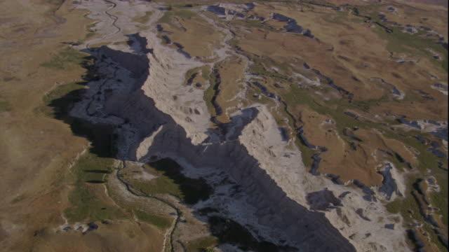 vídeos de stock e filmes b-roll de an eroded rocky mountain towers in an arid canyon. available in hd. - parque nacional de badlands