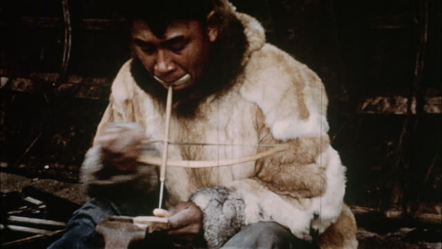 An Eskimo man uses a tool to do woodworking.