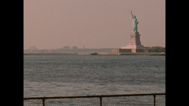an establishing shot captures the statue of liberty from across the new york harbor. - porto di new york video stock e b–roll