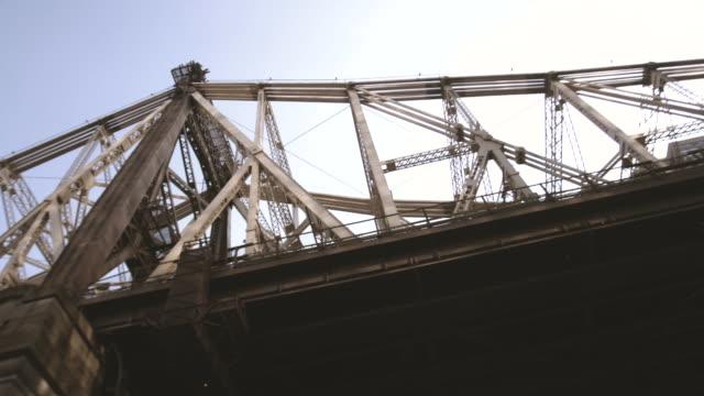an establishing shot of new york city's queensboro bridge on a warm, summer afternoon. - kantilever bildbanksvideor och videomaterial från bakom kulisserna