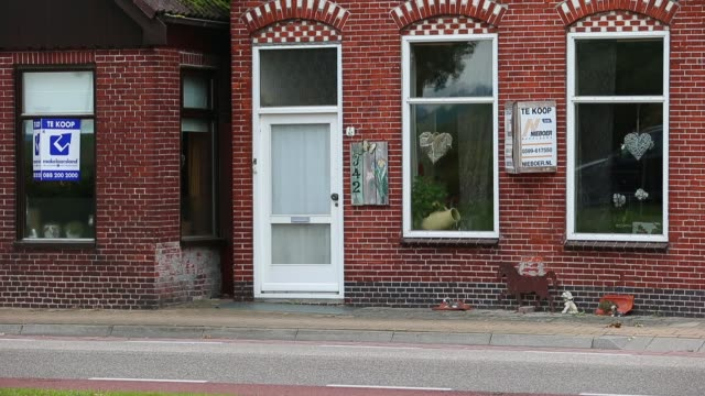 an estate agent's for sale sign stands near to residential property as a car drives past in nieuwe pekela netherlands on monday oct 14 a bus passes a... - 売り出し中点の映像素材/bロール