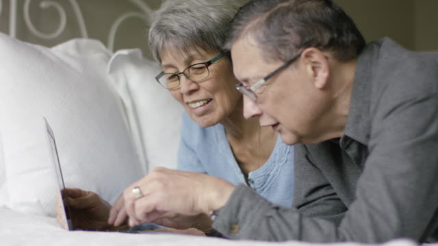 An Ethnic Senior Couple Lays on the Bed While Using a Laptop Computer