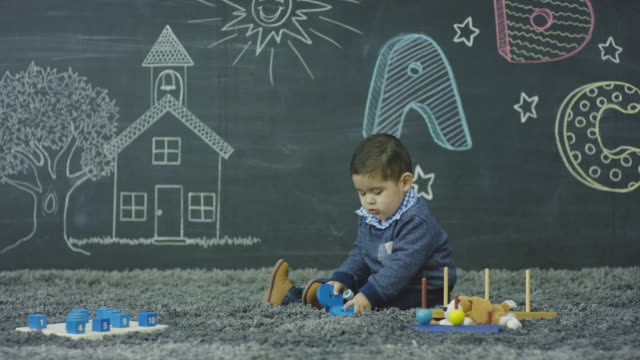 stockvideo's en b-roll-footage met een etnische peuter is spelen met speelgoed in opvang en glimlachen - fatcamera
