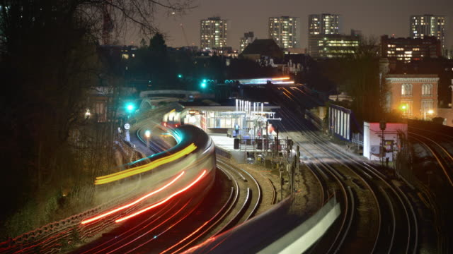 stockvideo's en b-roll-footage met an evening view of a north london tube station platform as trains arrive and stop commuters embark and disembark - metro platform