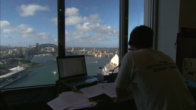 An event staff member in an observation tower looks out over Sydney Harbor.