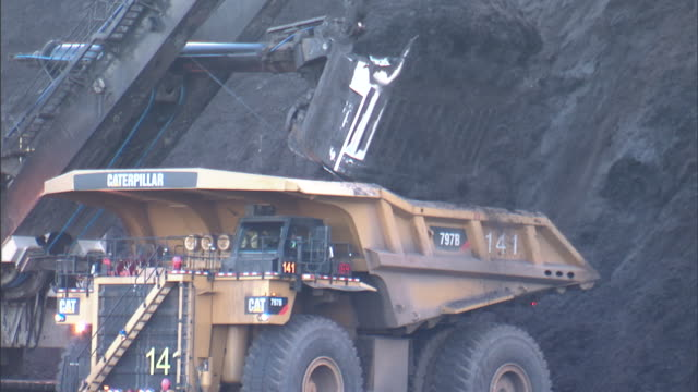 an excavator dumps coal into the back of a dump truck. - construction machinery stock videos & royalty-free footage