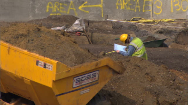 an excavator dumps dirt into a pile near a construction worker. - mechanical digger stock videos & royalty-free footage