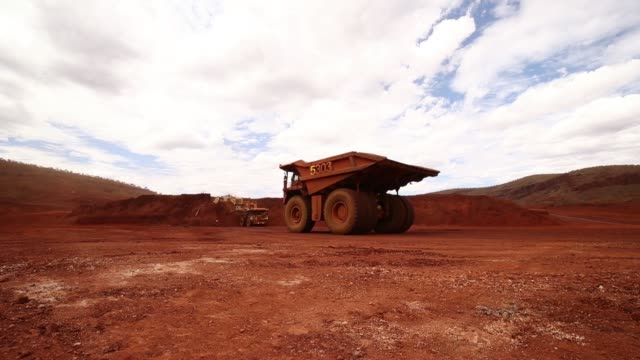 an excavator loads ore into autonomous dump trucks at fortescue metals group ltd's solomon hub mining operations in the pilbara region australia on... - iron ore stock videos & royalty-free footage