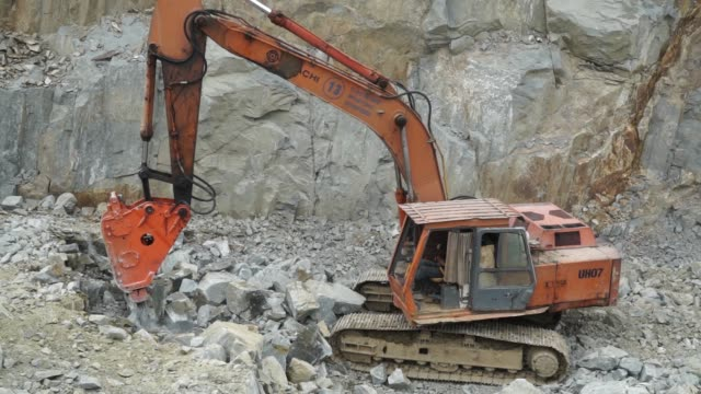an excavator operates in a quarry in kuching, sarawak, malaysia, on wednesday, april 14 a worker operates an excavator mounted hydraulic jackhammer... - サラワク州点の映像素材/bロール