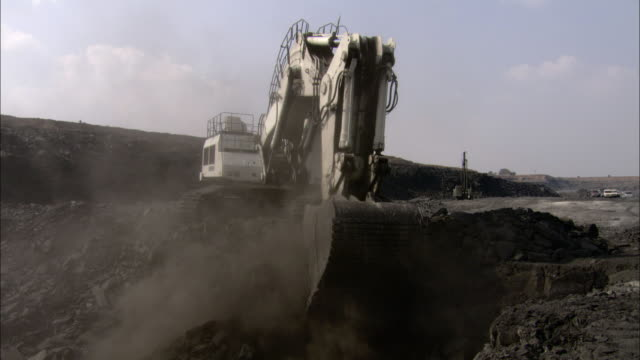 stockvideo's en b-roll-footage met an excavator scoops coal at a construction site. - bouwapparatuur