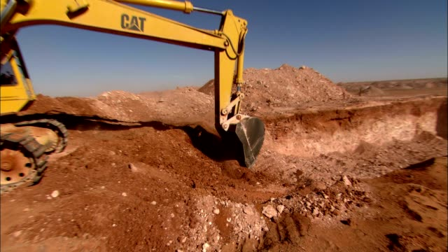 an excavator scoops up a load of dirt at a strip mine. - mechanical digger stock videos & royalty-free footage