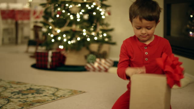 an excited five-year old caucasian boy opens a christmas present by the christmas tree on christmas day - christmas gift stock videos & royalty-free footage