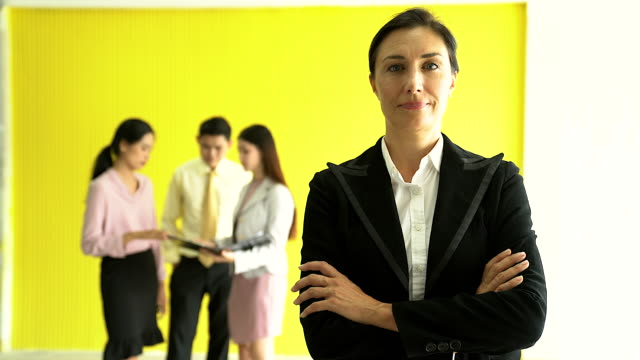 vídeos de stock e filmes b-roll de an executive senior businesswoman standing with arms crossed at the office and looking at the camera. - vestuário de trabalho formal