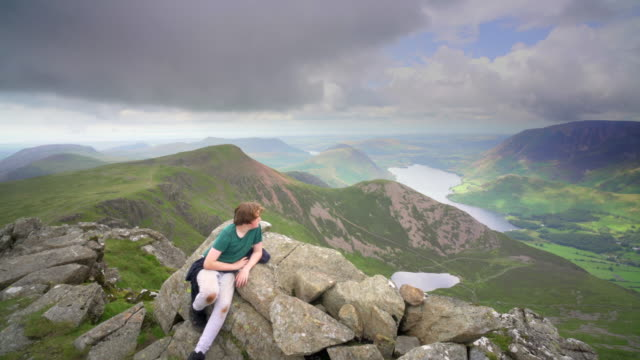 an exhausted teenage boy resting on the top of high stile, lake district, western fells, cumbria, uk - one teenage boy only stock videos & royalty-free footage