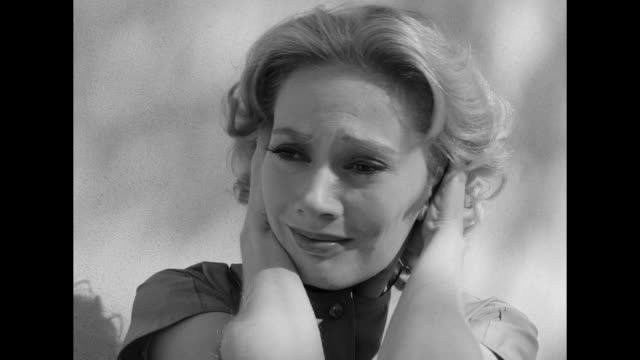 1962 an exhausted woman pauses on the sidewalk to relieve her stress - bestürzt stock-videos und b-roll-filmmaterial