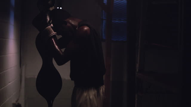 vidéos et rushes de slo mo. an exhausted young boxer hangs onto a punching bag after training with his boxing coach at a professional boxing gym - s'appuyant