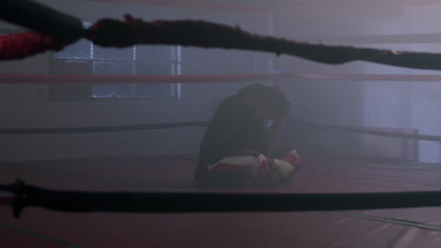 vidéos et rushes de slo mo. an exhausted young boxer sits with his legs crossed and rubs his head inside a boxing ring after training with his boxing coach at a professional boxing gym - ring de boxe