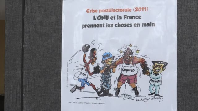 vídeos de stock, filmes e b-roll de an exhibition of satirical cartoons charts ivory coasts turbulent history over the past 20 years with politicians rebels the army and police all in... - sátira