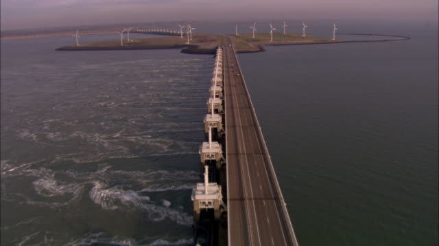 an expansive bridge extends across the ocean to a wind turbine farm. - sustainable energy stock videos & royalty-free footage