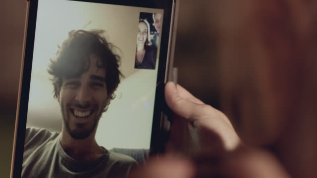 vídeos de stock e filmes b-roll de an expectant couple tells her brother it's a boy via voice chat on a tablet - festa