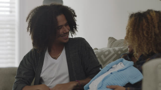 cu of an expecting african-american couple opening baby boy gifts at home on their sofa - 赤ちゃんの靴点の映像素材/bロール